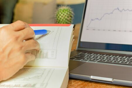 Businessman pointing on data chart with pen while working iwith laptop Stok Fotoğraf