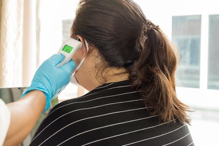 Woman examines patient temperature in the ear using electronic thermometer.