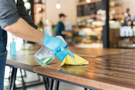 Waiter cleaning the table with disinfectant spray and microfiber cloth in cafe.