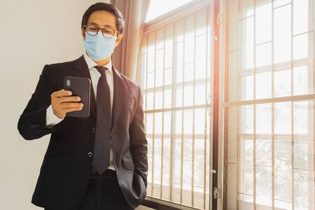 Businessman wearing protective mask preventing covid - 19 using cell phone.