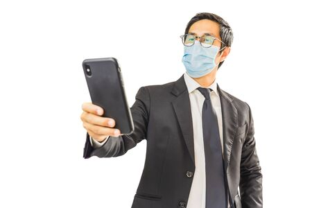 Businessman wearing face mask preventing covid - 19 holding cell phone.