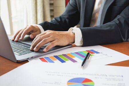 Geschäftsmann, der an Laptop mit Diagrammvorratdiagramm auf Tabelle arbeitet. Standard-Bild