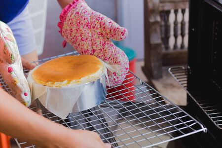 Woman takes basque burnt cheesecake out of the oven.