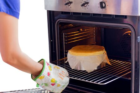Woman takes basque burnt cheesecake out of the oven isolated.