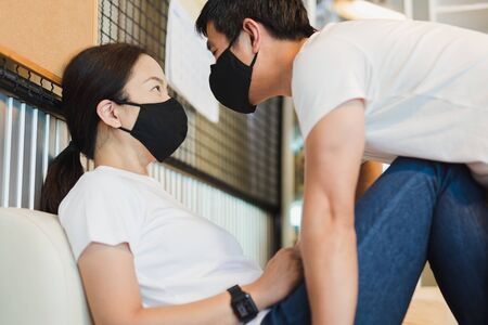 Couple wearing protective mask and staring at each others pandemic concept. Stock fotó