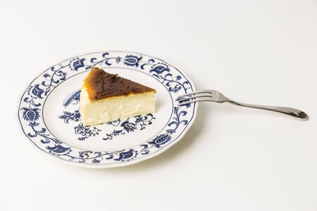 Basque Burnt Cheesecake with fork isolated in white background