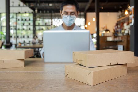 Selected ocus parcel on table with man wearing medical mask work on laptop.