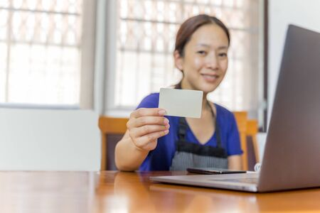 Businesswoman with apron holding credit card with open laptop on table work from home concept.