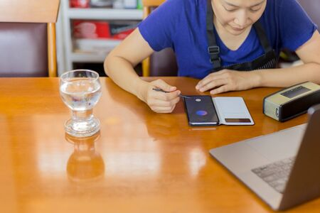 Businesswoman with apron analysts small business strategy at home with laptop on table. Stock Photo