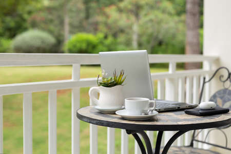 Image of laptop with coffee cup and plant on table in balcony with garden view. 免版税图像