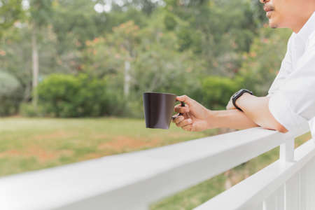 Man relaxjng hand holding coffee mug while standing on balcony.