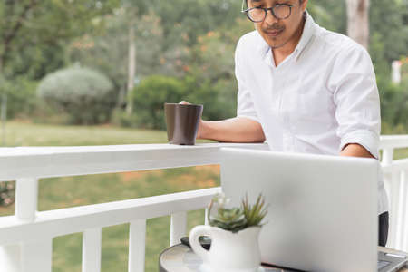 Businessman in glasses holding coffee while working on laptop.