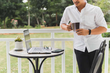 Businessman relax standing on terrace hand holding coffee with laptop on table. Banque d'images