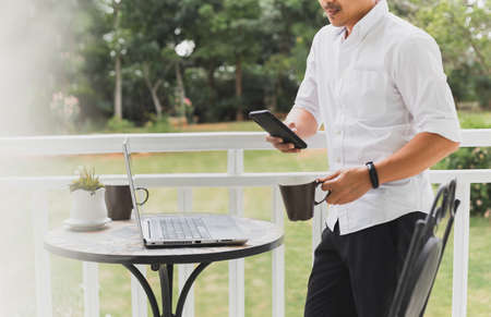 Businessman checking mobile phone standing in balcony with laptop on table.