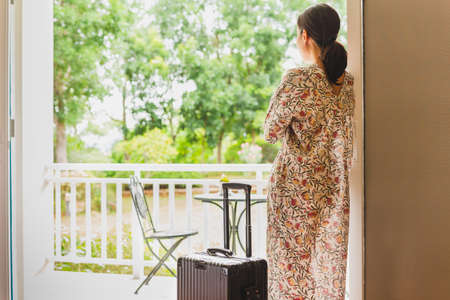 Tourist woman standing near window looking at beautiful garden view with her luggage in hotel bedroom.