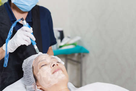 Woman having stimulating facial treatment at professional clinic. Stock Photo