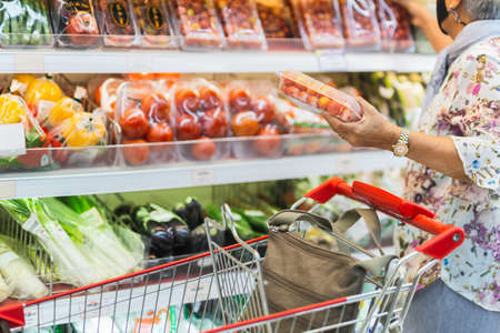 Senior woman wearing protective mask doing grocery shopping in supermarket.