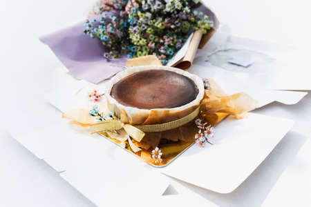 Chocolate basque burnt cheesecake with bouquet flower on table.