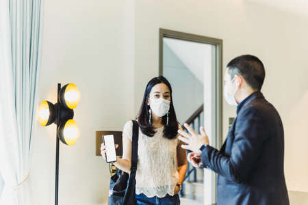 Woman in protective mask video call on cell phone with male real estate agent.