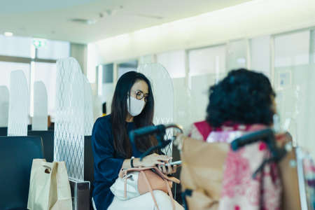 Woman in protective mask using cell phone sitting in partition with her senior mother in hospital.