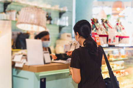 Woman with protective mask paying bill at cashier counter in cafe.
