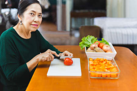 Healthy eating, senior woman chopping tomato for cooking.