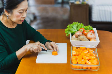 Healthy eating, senior woman chopping carrots for cooking.