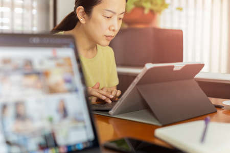 Asian business woman working on laptop computer at home. Standard-Bild