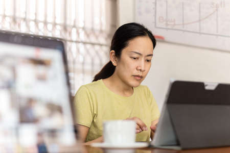 Businesswoman working from home typing laptop including pen and smartphone.