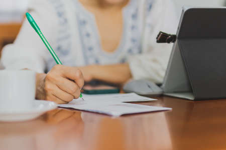 Female hand writing on financial papers while paying bills online using laptop.