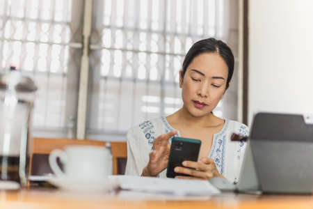 Businesswoman using mobile phone while working on laptop at home.