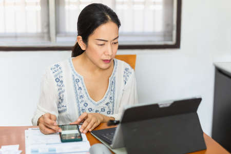 Woman working on laptop and cell phone at home.