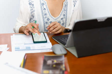 Businesswoman using cell phone calculating bills at home office table.