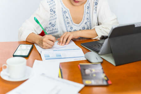 Woman paying bills online and writing notes at home. Standard-Bild - 163302752