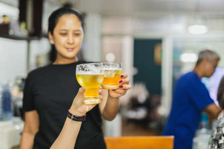 Woman hands clinking glasses of beer on family party. Standard-Bild