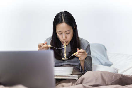 Businesswoman eating instant noodle in bed while working on laptop at home.