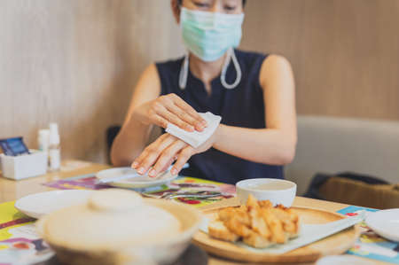 Woman in medical mask cleaning her hands with a wet wipes in restaurant.