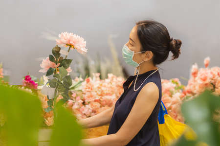 Woman in protective mask buying artificial flowers