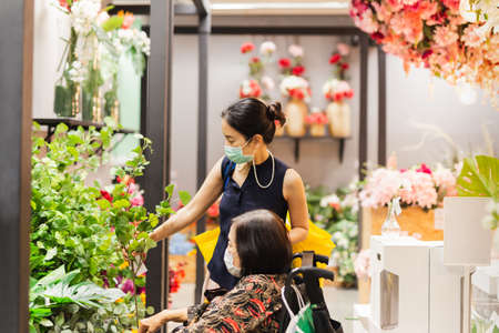 Senior woman with daughter in protective mask chooses artificial flower branch in shop.