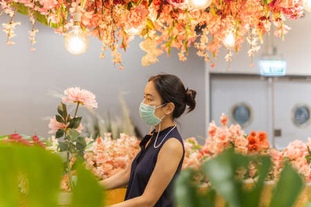 Woman in medicail mask chooses artificial flowers in flower shop. Standard-Bild