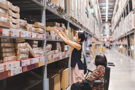 Woman in protective mask hand reaching box in Warehouse interior shelves. Standard-Bild