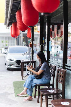 Woman wearing face mask using mobile waiting for table outside restaurant.