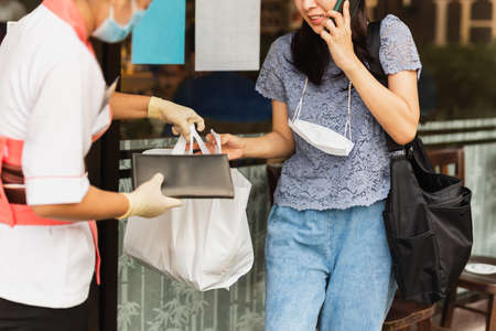 Waitress with protective mask giving take out food bag to woman customer. Standard-Bild