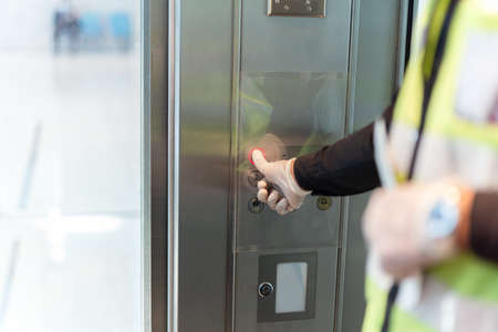 Security man hand in protective glove against virus presses lift button.