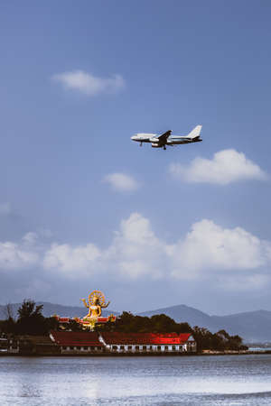 Passenger airplane flying over above big buddha in koh samui island.