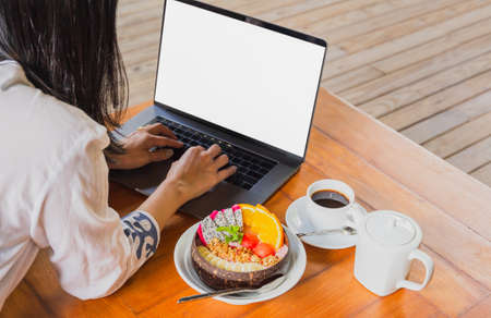Woman working on laptop while breakfast with bowl of smoothy and coffee.