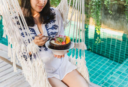 Woman holding bowl of smoothy sitting on hammock by swimming pool. Standard-Bild