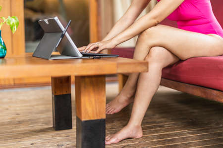 Woman in pink swimming suit using laptop on vacation.