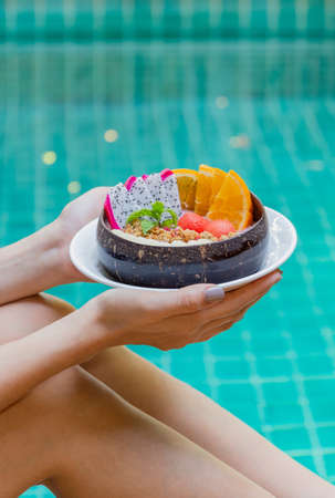 Woman holding smoothie bowl and fruits by swimming pool.