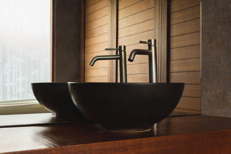 Bathroom interior black sink with silver faucet and mirror on wooden top.